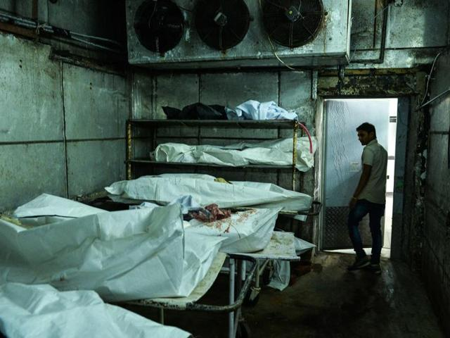 A medic walks through a cold storage unit as he inspects a morgue in New Delhi. Inside the cold storage rooms, bodies take up every square inch of the blood-stained floors.
