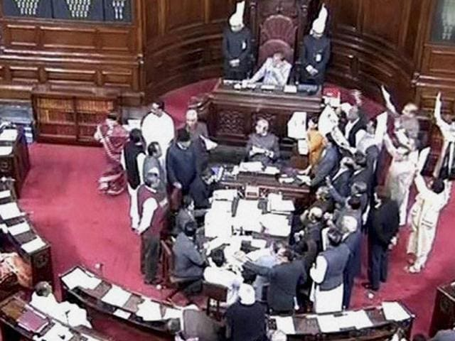 Opposition members protest in the well of the Rajya Sabha in New Delhi on Monday.