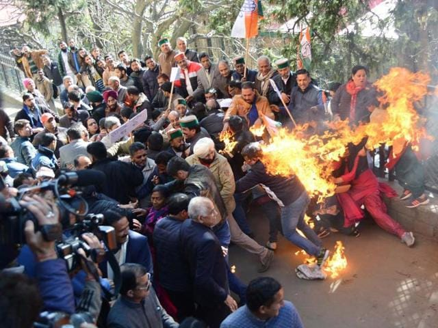 Congress workers run after they catch fire while trying to burn Prime Minister's effigy in Shimla on Monday.