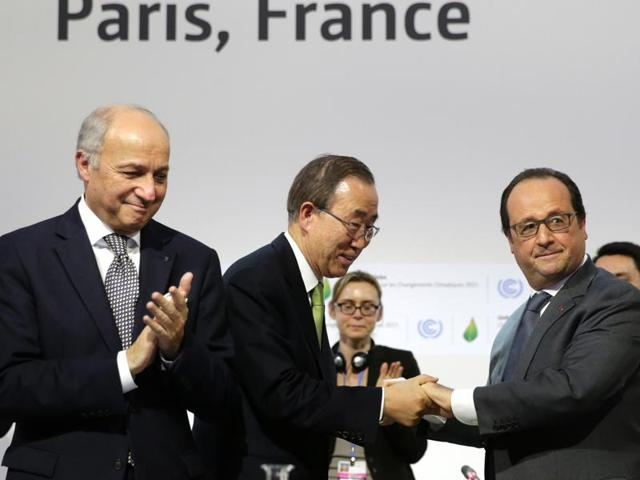 French President Francois Hollande (R) shakes hands with UN secretary general Ban Ki-moon next to French foreign minister and COP21 president Laurent Fabius (L) during the final session of the COP21 United Nations climate change conference in Le Bourget near Paris on Saturday.