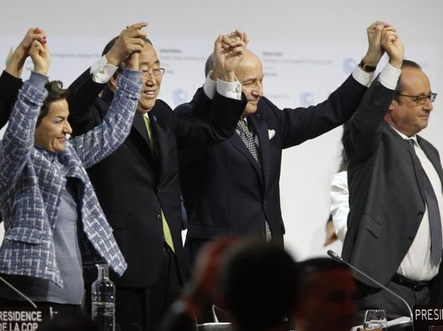 Foreign affairs minister and president-designate of COP21 Laurent Fabius (C), raises hands with secretary general of the United Nations Ban Ki Moon (2-L) and France's President Francois Hollande (R) after adoption of a historic global warming pact at the COP21 Climate Conference.