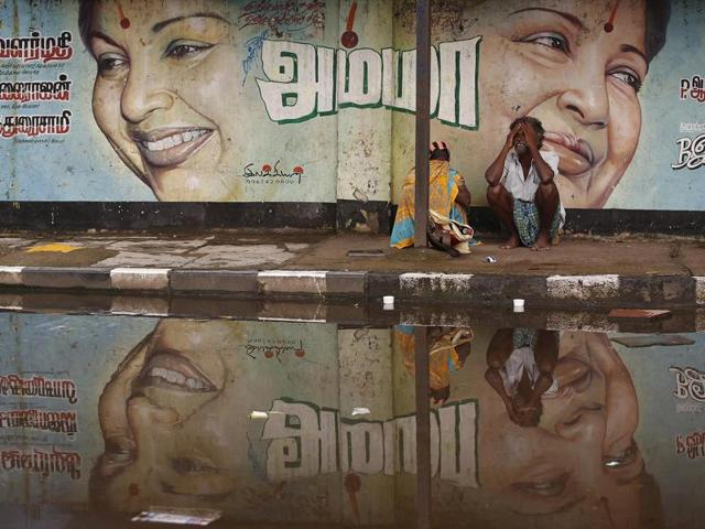 A flood-affected couple sits along a flooded roadside under a picture of Jayalalithaa, chief minister of the Tamil Nadu, in Chennai.