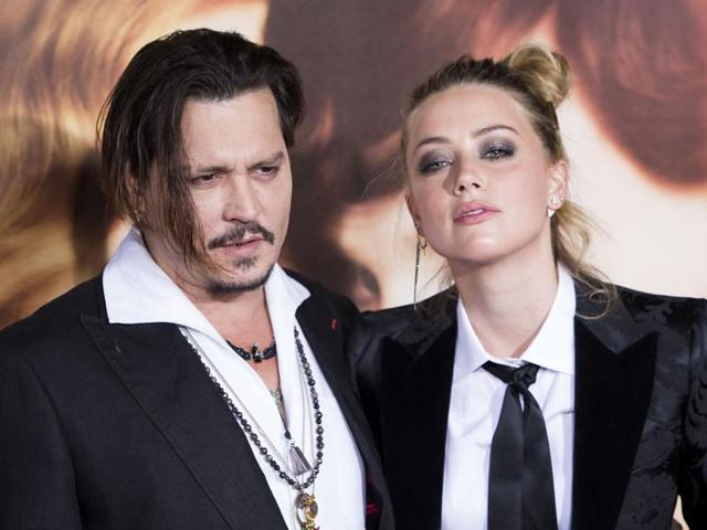 Johnny Depp (L) and his wife, actress Amber Heard, as they attend the Los Angeles Premiere of The Danish Girl. Heard will face trial in Australia in April, 2016 for allegedly smuggling two dogs into the country.