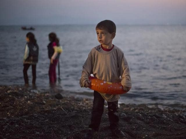 A Syrian migrant boy still wearing a swimming ring stands on the beach upon his arrival with other migrants by a dinghy at the southeastern Greek island of Kos, Greece.