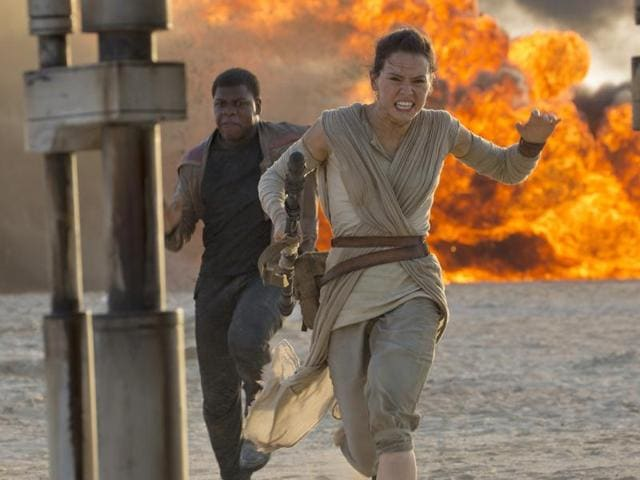 This photo provided by Disney/Lucasfilm shows Daisy Ridley, right, as Rey, and John Boyega as Finn, in a scene from the film, Star Wars: The Force Awakens, directed by JJ Abrams. Early screenings of the film began Thursday.