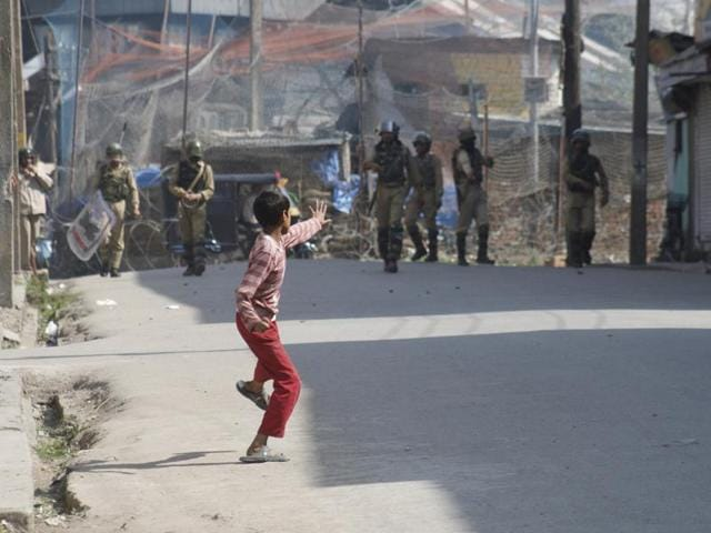File photo of Kashmiri kid throwing stones at Indian paramilitary forces during a protest, in Srinagar.