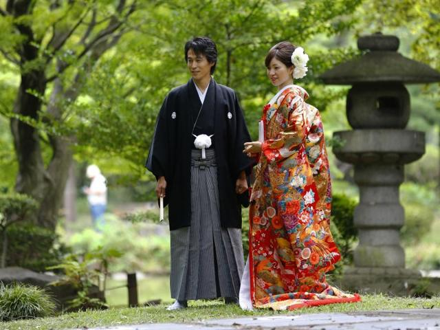 A couple dressed in Japanese traditional wedding Kimonos pose for a wedding photograph at Hibiya park in Tokyo.