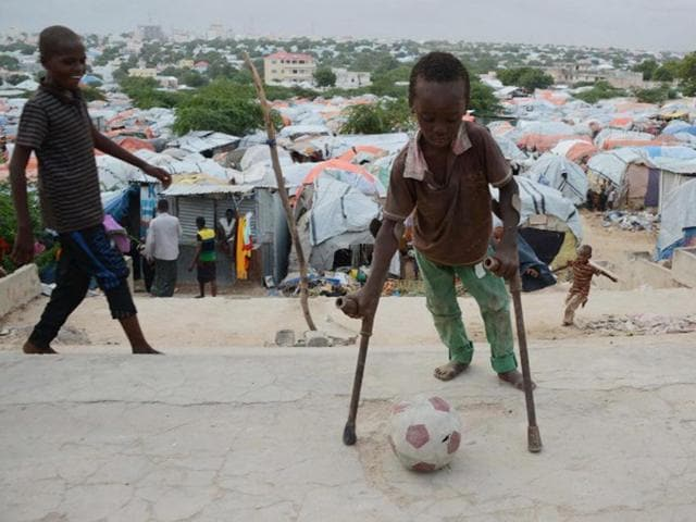 A Somali boy in crutches plays with a football in front of makeshift shelters at the Sayyid camp in the Howlwadaag district of Mogadishu.