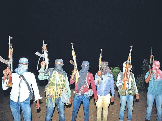 PLFI members show their firearms in a forest near Jharkhand-Odisha border.