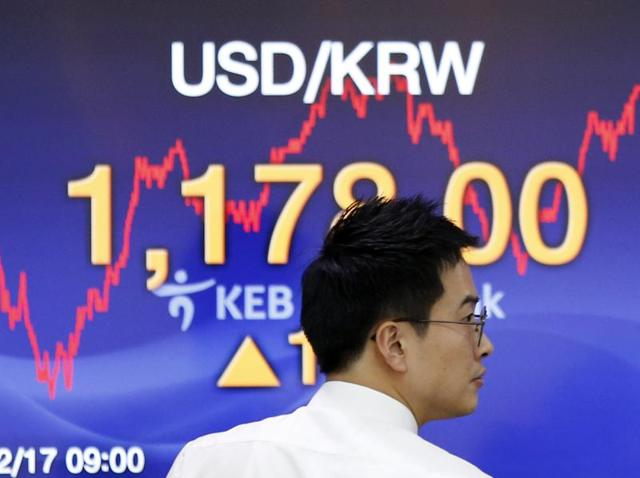 A currency trader walks by the screen showing the foreign exchange rate between the US dollar and the South Korean won. Asian stocks posted broad gains on Thursday after the Federal Reserve ended protracted uncertainty in markets by raising interest rates for the first time in nearly a decade.