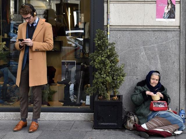 """A man consults a mobile phone beside a woman begging on the pavement in Salamanca, an upscale neighbourhood of Madrid. The number of millionaires in Spain rose by 40% to 178,000 last year from 2008 when the crisis started while the number of people living with """"severe material deprivation"""" in the country has doubled since 2007 to just over three million last year, according to a study by anti-poverty agency Oxfam."""
