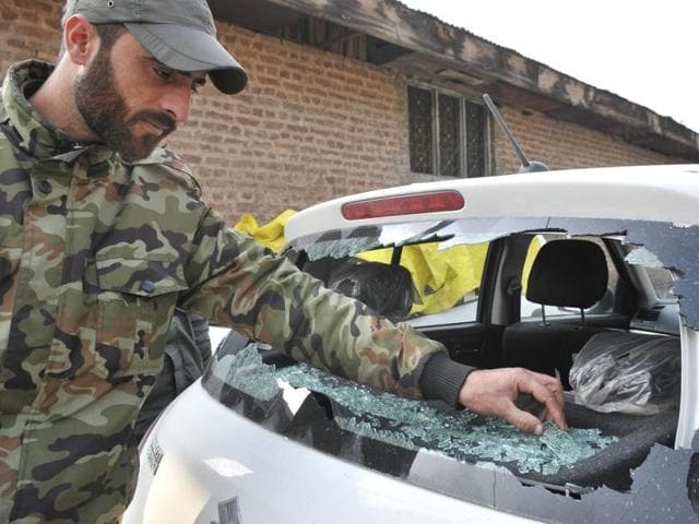 Policeman examining the broken wind shield of a vehicle after a grenade explosion in Seki Dafar chowk of Srinagar on Thursday.