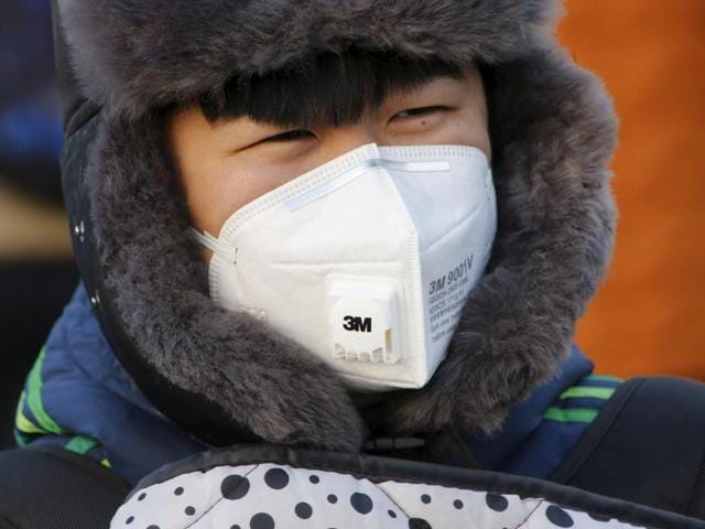 A man wears a protective mask makes her way as China warned residents across a large part of northern China to prepare for a wave of choking smog arriving over the weekend, in Beijing, China.