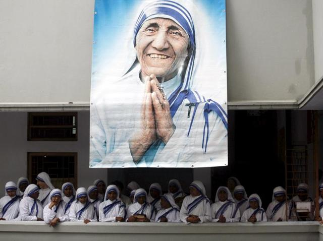 Catholic nuns from the Missionaries of Charity, the global order of nuns founded by Mother Teresa, pray at her tomb in Kolkata on her death anniversary. Mother Teresa will be made a saint of the Roman Catholic Church, the Vatican said on Friday.(Reuters File Photo)