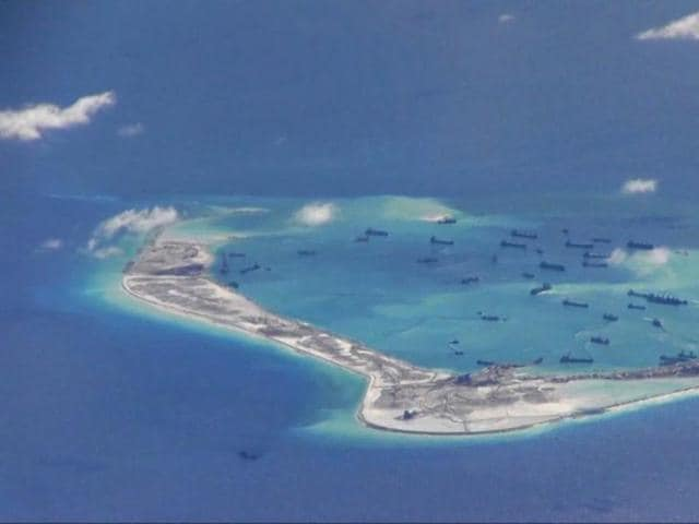 Chinese dredging vessels are purportedly seen in the waters around Mischief Reef in the disputed Spratly Islands in the South China Sea in this still image from video taken by a P-8A Poseidon surveillance aircraft provided by the United States Navy.