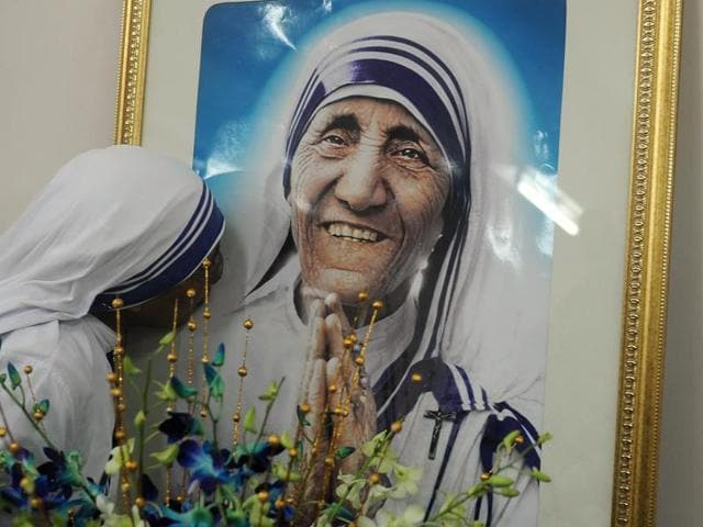 A nun belonging to the order of the Missionaries of Charity kisses a picture of Mother Teresa during a mass service to commemorate her death anniversary at the Missionaries of Charity house in Kolkata on September 5, 2012.