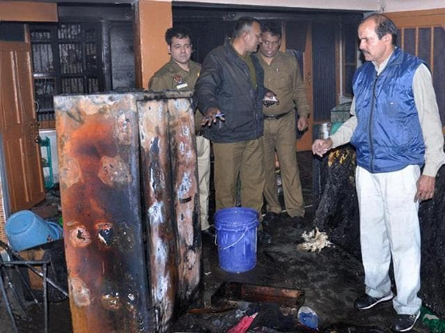 Fire officials at a house where a 10-year-old girl died in Manimajra on Thursday.(Sant Arora/HT Photo)