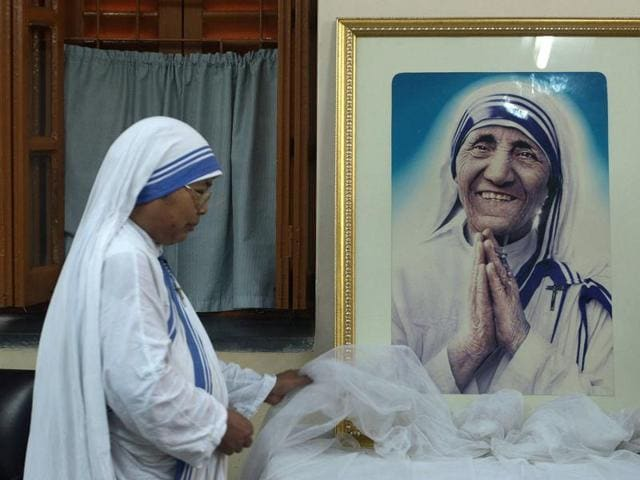 A nun of the Missionaries of Charity decorates a picture of Mother Teresa prior to a special prayer service at Mother House in Kolkata.
