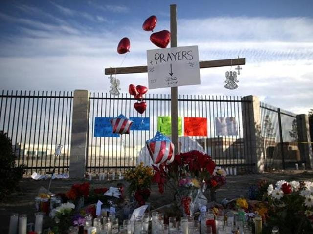 People visit a makeshift memorial for the victims of a mass shooting near the Inland Regional Center in San Bernardino.