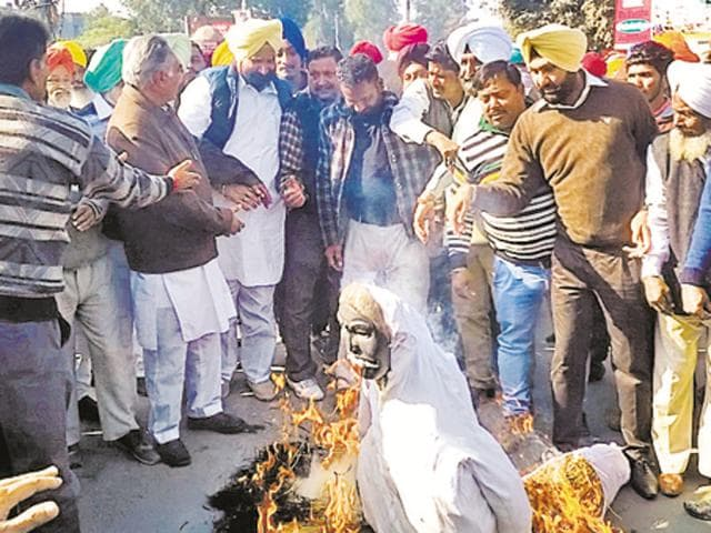 Congress workers burning effigies of Modi and Badal governments in Gurdaspur on Saturday.