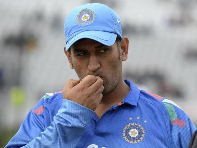 India's Mahendra Singh Dhoni looks on before the coin toss before the third one-day international cricket match against England at Trent Bridge cricket ground, Nottingham, England August 30, 2014. REUTERS/Philip Brown/Files