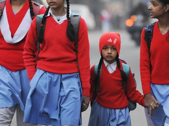 School children go to school packed in woollens. Delhiites wake up to a cold morning on Tuesday, December 15, 2015.