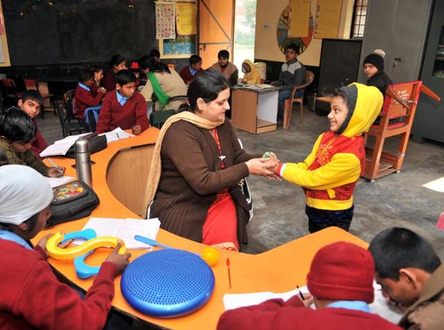 An inclusive education volunteer teaching children with special needs at resource centre, Abadpura, in Jalandhar on Friday.(HT Photo)