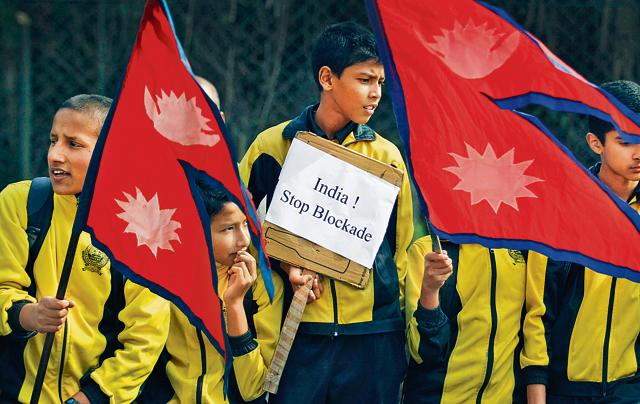 Nepalese schoolchildren hold national flags and placards as they take part in a protest rally on the outskirts of Kathmandu during an ongoing dispute between Nepal and India.The border blockade by Madhesis to protest against the Constitution and the resulting crisis is the other.