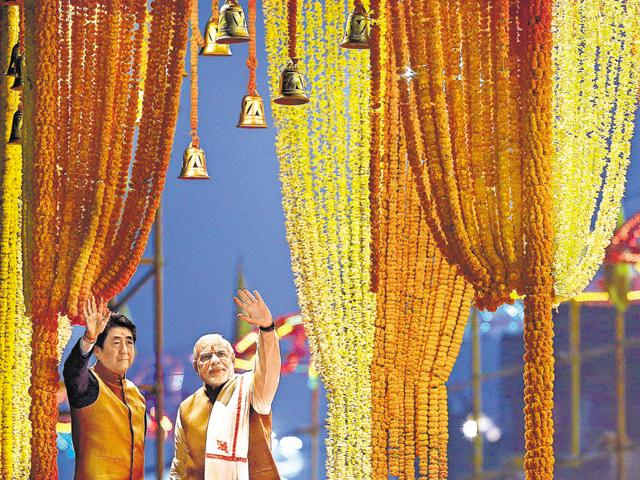 Japan's Prime Minister Shinzo Abe (L) and his Indian counterpart Narendra Modi wave to the crowd after watching the 'Aarti' during evening prayers on the banks of river Ganga at Varanasi.