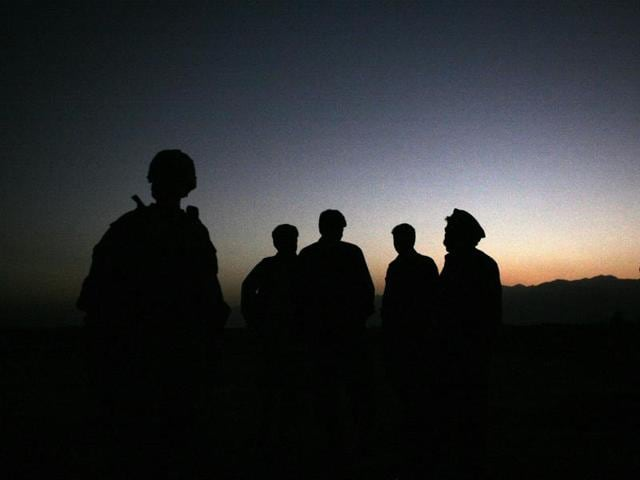 In this  file photo, U.S. Army soldiers stand with Afghan policemen before a joint patrol of Qalanderkhail, outside of Bagram Air Field in Afghanistan. An Afghan official says that a suicide bomber has killed three foreign troops in an attack on a joint Afghan-NATO foot patrol on Monday, Dec. 21, 2015. Mohammad Asim Asim, governor of Parwan province said an attacker on a motorcycle rammed a group of eight troops as they patrolled a village near Bagram Airfield, 45 kilometers (28 miles) north of Kabul.