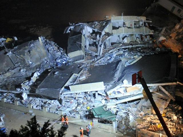 Firefighters stand next to collapsed buildings after a landslide hit an industrial park in Shenzhen, Guangdong province, China.(Reuters Photo)