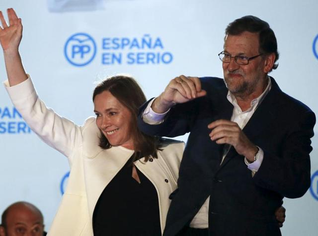 Spain's Prime Minister and People's Party (PP) candidate Mariano Rajoy gestures while addressing supporters from a balcony at the party headquarters next to his wife Elvira Fernandez after results were announced in Spain's general election in Madrid.