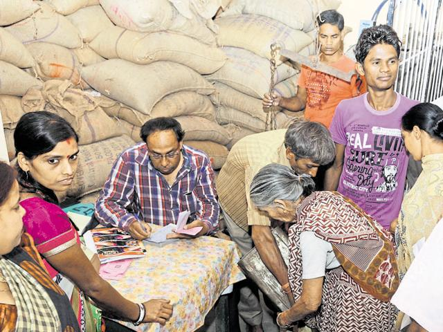 People purchase food grains distributed by a public distribution system shop in Ranchi on Sunday.
