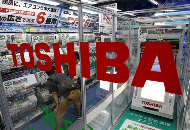 FILE - In this July 20, 2015 file photo, shoppers watch air conditioners displayed at an electronics store in Tokyo. Scandal-plagued Japanese manufacturer Toshiba Corp. is cutting 6,800 jobs after projecting a net loss of 550 billion yen ($4.5 billion) for the fiscal year through March 2016. Toshiba said Monday, Dec. 21, 2015, it will slash the jobs in its personal computer, video product and consumer electronic businesses. The job cuts equal about 3 percent of Toshiba's overall employees. (AP Photo/Shizuo Kambayashi, File)