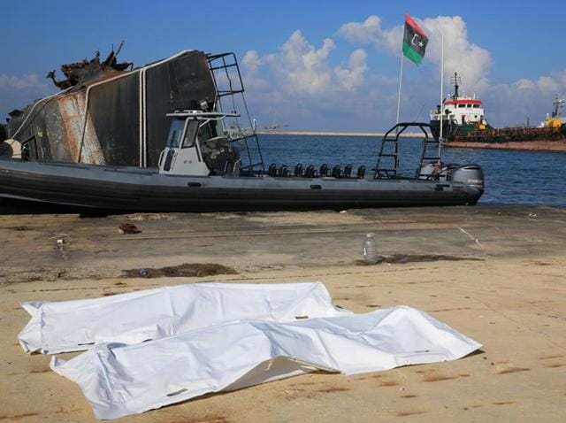 The covered bodies of two migrants who died after their boat, which was headed to Italy, sank off the coast of Libya on December 21, 2015.