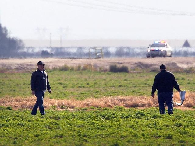 Investigators search a field for debris from an aircraft crash in Bakersfield, California.