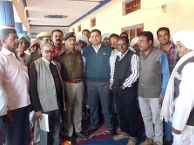 Banswara superintendent of police Anand Sharma (centre, in blue sweater) at the function organised to felicitate the locals for keeping their village litigation-free, in Daulatpura.(HT Photo)