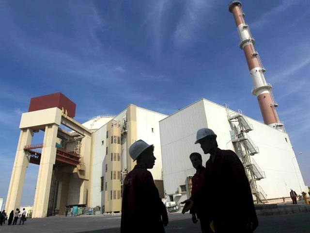 Iranian workers stand in front of the Bushehr nuclear power plant in this file photo. Russia will start building two nuclear reactors in Iran next week after  a historic deal between Iran and world powers in July that ended a decade-long standoff over Tehran's nuclear programme.