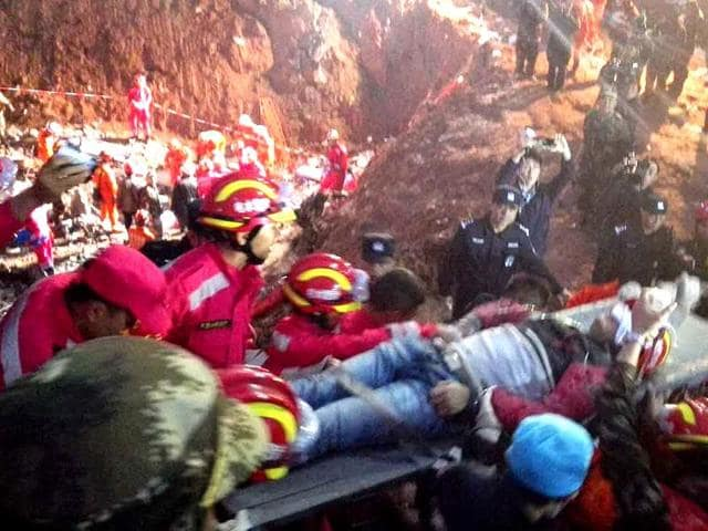 In this photo provided by China's Xinhua News Agency, a survivor is rescued at the site of landslide at an industrial park in Shenzhen, south China's Guangdong Province.