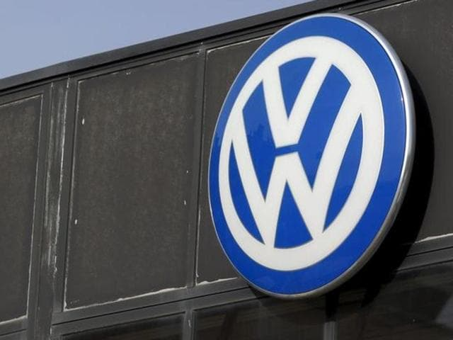 A worker wearing a protective mask stands next to a Volkswagen logo at a dealership in Madrid, Spain, December 16, 2015.