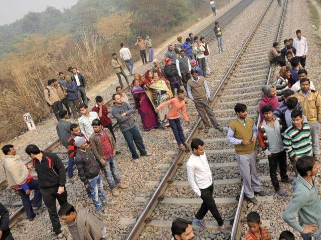 Citizens gather at the site where a Ranchi-bound BSF aircraft narrowly missed an express train and crashed in west Delhi's Dwarka area after developing a technical snag ( Vipin Kumar/ Hindustan Times)