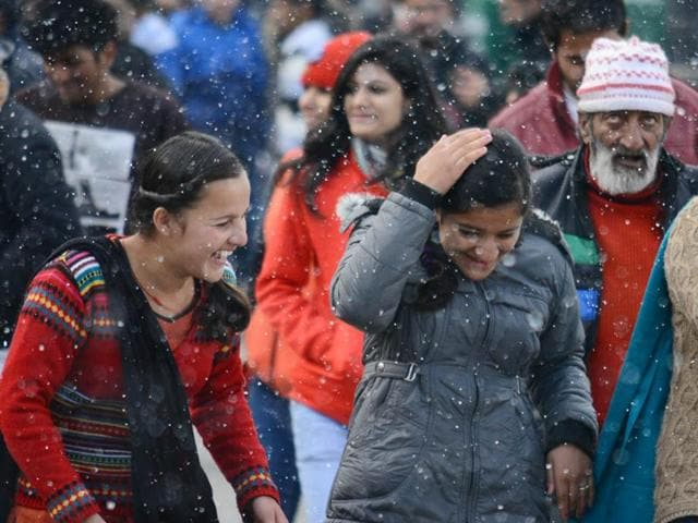 Girls enjoying season's first snow at the Mall Road in Shimla on Wednesday.