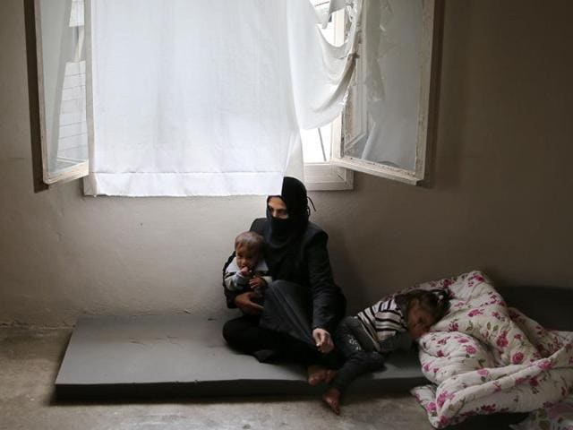 Syrian refugee Hind Salem, who fled with her family from the central Syrian town of Palmyra, from Russian airstrikes, sits on the ground with her kids at their unfurnished home, in the Turkish-Syrian border city of Reyhanli, southern Turkey.  A new report by a human rights watchdog group accuses Russia of using cluster munitions and unguided bombs on civilian areas in Syria in attacks that it says have killed hundreds of people.