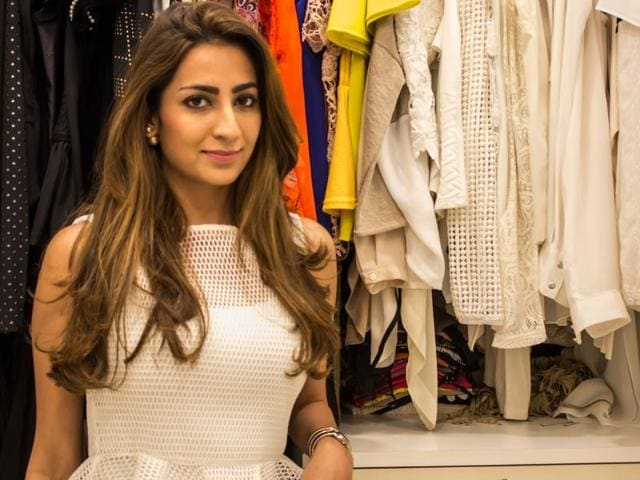 Nadine Dhhody shows us around her closet dressed in a structured white top, white jeans, pearl ear jackets and nude heels