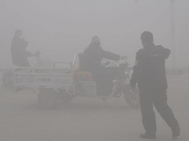 A policeman talks to the driver of a motor-tricycle on a road amid heavy haze in Handan city in northern China's Hebei province. Hebei, a province which neighbours Beijing and is regarded as China's most polluted, issued its first red alert for smog on December 24.(AP)