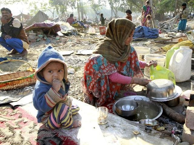 People sit near their demolished houses an anti-encroachment drive conducted by the Indian Railways at Shakur Basti in New Delhi.