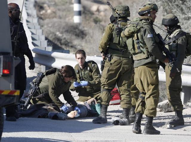 Israeli soldiers work around the body of a Palestinian assailant after he was shoot dead in the West Bank city of Hebron.