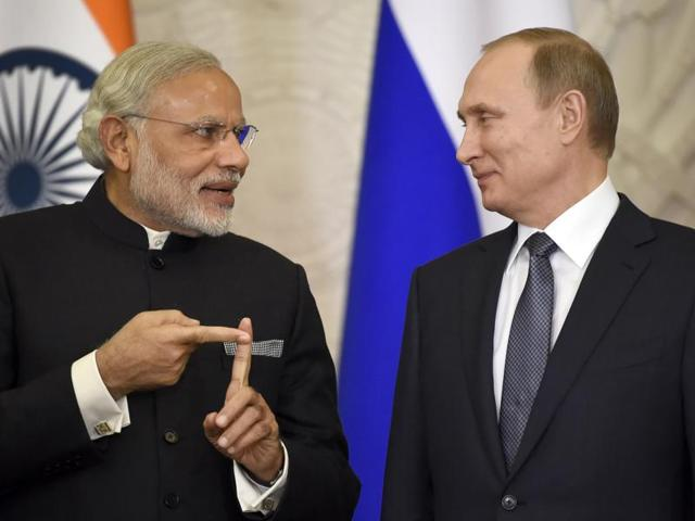 Russian President Vladimir Putin, right, and Indian Prime Minister Narendra Modi arrive to attend a meeting with Russian and Indian officials and businessmen in the Kremlin in Moscow.