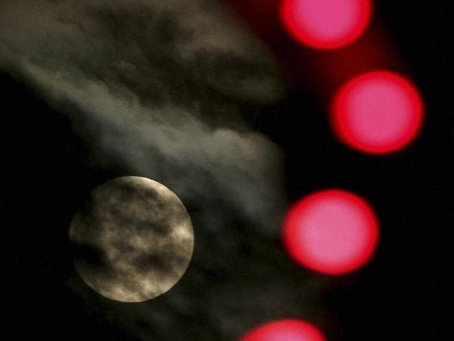 The nearly full-moon is seen among Christmas lights at a holiday display in Lenexa, Kan.