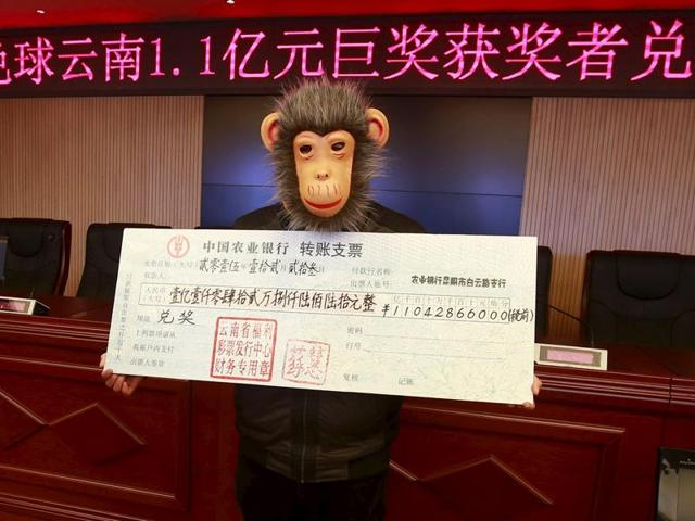 A man wears a monkey mask as a disguise to receive a cheque of over 110 million yuan ($17 million) after winning a lottery jackpot in Kunming, Yunnan province of China.
